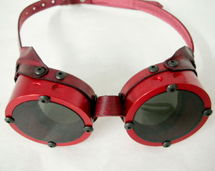 These Goggles have been machined from solid Engineering Grade Aluminum. They feature grey acrylic lenses which are fully removable. They also come with a pair of colored lenses of your choice. Please indicate whether you would like Blue, Red, or Yellow colored lenses.  These goggles have a Red Anodized finish.